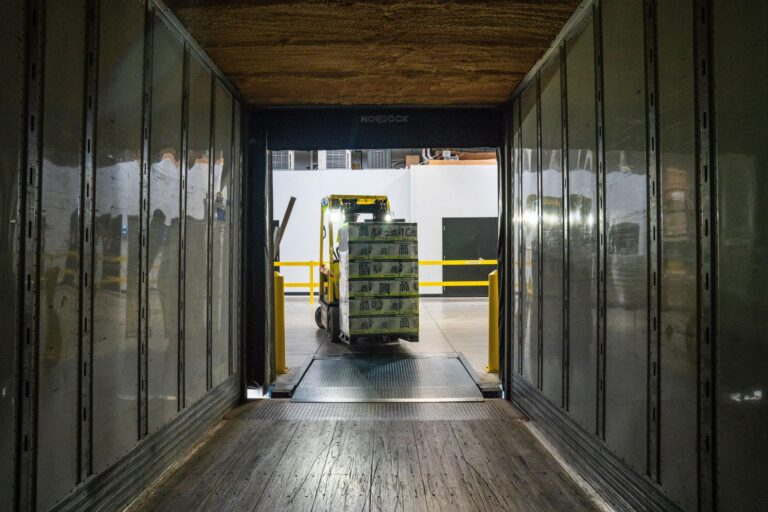 material handler forklift putting pallets in truck